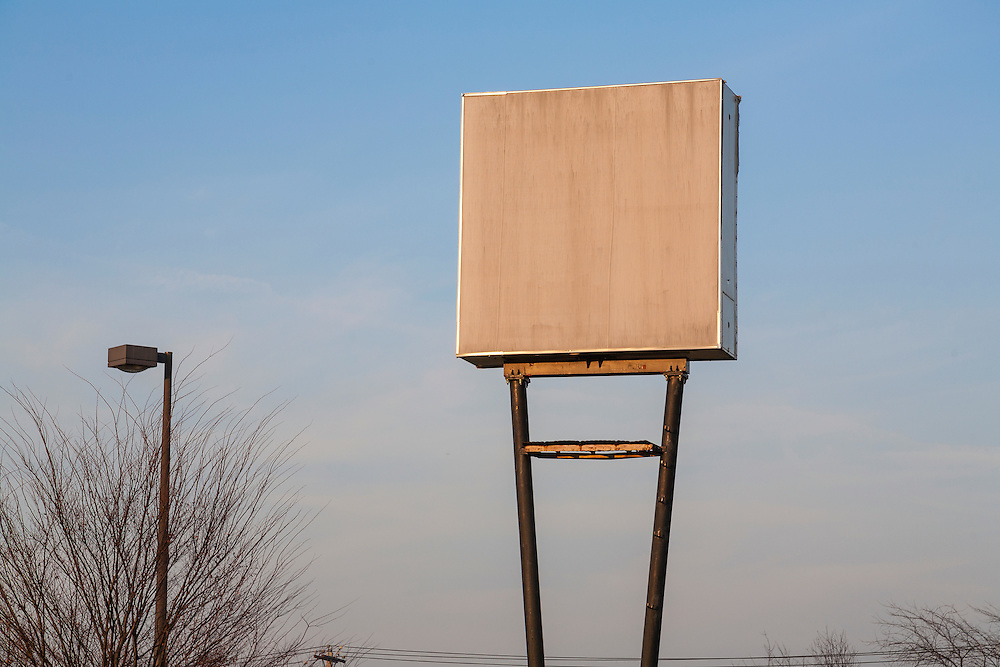 Blank sign makes a canvas for the setting sun's light stark along with bare trees and lightpost against a blue sky