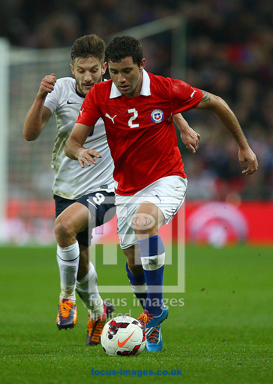 Picture by Rob Fisher/Focus Images Ltd +44 7450 945824<br /> 15/11/2013<br /> Adam Lallana of England and Eugenio Mena of Chile battle for the ball during the Friendly match at Wembley Stadium, London.