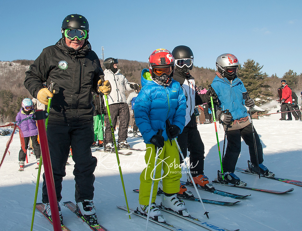 Gunstock Ski Club U10 coach Klaus Buttinger with Finn Henderson, Luke Stafford and Aaron St Gelais as they prepare to load the Panorama lift.  (Karen Bobotas/for the Laconia Daily Sun)