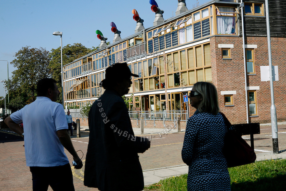 Tourists are taking part to an organised tour of the buildings in the BedZED housing complex on Thursday, Sep. 6, 2007, in London, UK. BedZED or the Beddington Zero Energy Development, is an environmentally-friendly housing development near Wallington, England in the London Borough of Sutton. It was designed by the architect Bill Dunster who was looking for a more sustainable way of building housing in urban areas in partnership between the BioRegional Development Group and the Peabody Trust. There are 82 houses, 17 apartments and 1,405 square meters of work space were built between 2000. The project was shortlisted for the Stirling Prize in 2003. The project is designed to use only energy from renewable source generated on site. In addition to 777 square meters of solar panels, tree waste is used for heating and electricity. The houses face south to take advantage of solar gain, are triple glazed and have high thermal insulation while most rain water is collected and reused. Appliances are chosen to be water efficient and use recycled water wherever possible. Low impact building materials were selected from renewable or recycled sources and were all originating within a 35 mile radius of the site to minimize the energy required for transportation. Also, refuse collection facilities are designed to support recycling and the site encourage eco-friendly transport: electric and LPG cars have priority over petrol/diesel cars, and electricity is provided by parking spaces appositely built for charging electric cars.