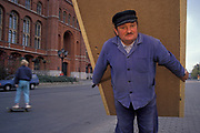 A year after the fall of the Berlin Wall and the end of the Communist Eastern Bloc, workman carries a wooden panel or door in a Berlin street, on 4th November 1990, in Berlin, Germany.
