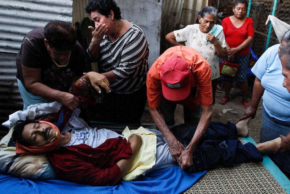In this photo taken Thursday, Jan. 19, 2012, Relatives dress the body of the recently dead Jesus Flores, 51, chronic renal failure patient and former worker irrigator a mason of the San Antonio sugarmill, inside of her house in Chichigalpa, Nicaragua. in this Wednesday, Jan. 4, 2012 photo. Flores, 51, who died of chronic kidney disease on Jan. 19, 2012, worked as an irrigator and construction worker for 23 years at the San Antonio sugar plantation and mill. A mysterious epidemic is devastating the Pacific coast of Central America, killing more than 24,000 people in El Salvador and Nicaragua since 2000 and striking thousands of others with chronic kidney disease at rates unseen virtually anywhere else. Many of the victims were manual laborers or worked in the sugarcane fields that cover much of the coastal lowlands.