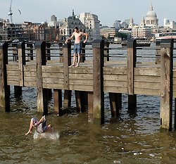 © Licensed to London News Pictures. 15/07/2013. London, UK. Two men jump jump from a jetty into the River Thames on the South Bank in London on 14 July 2013.  The UK is experiencing a heatwave with temperatures expected to reach 30 degrees Celsius again today. Photo credit : Vickie Flores/LNP