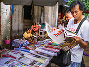 16 JUNE 2013 - YANGON, MYANMAR: A man reads a newspaper at a street side newsstand in Yangon. The Burmese newspaper industry has enjoyed explosive growth this year after private ownership was allowed in 2013. Private newspapers were shut down under former Burmese leader Ne Win in the early 1960s. The revitalized private press is a sign of the dramatic changes sweeping Myanmar, formerly Burma, in the last three years.      PHOTO BY JACK KURTZ