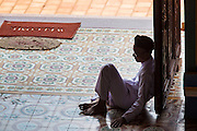 """29 MARCH 2012 - TAY NINH, VIETNAM:   A Cao Dai adherent sits in the shade before the noon prayer service at the Cao Dai Holy See in Tay Ninh, Vietnam. Cao Dai (also Caodaiism) is a syncretistic, monotheistic religion, officially established in the city of Tây Ninh, southern Vietnam in 1926. Cao means """"high"""" and """"Dai"""" means """"dais"""" (as in a platform or altar raised above the surrounding level to give prominence to the person on it). Estimates of Cao Dai adherents in Vietnam vary, but most sources give two to three million, but there may be up to six million. An additional 30,000 Vietnamese exiles, in the United States, Europe, and Australia are Cao Dai followers. During the Vietnam's wars from 1945-1975, members of Cao Dai were active in political and military struggles, both against French colonial forces and Prime Minister Ngo Dinh Diem of South Vietnam. Their opposition to the communist forces until 1975 was a factor in their repression after the fall of Saigon in 1975, when the incoming communist government proscribed the practice of Cao Dai. In 1997, the Cao Dai was granted legal recognition. Cao Dai's pantheon of saints includes such diverse figures as the Buddha, Confucius, Jesus Christ, Muhammad, Pericles, Julius Caesar, Joan of Arc, Victor Hugo, and the Chinese revolutionary leader Sun Yat-sen. These are honored at Cao Dai temples, along with ancestors.     PHOTO BY JACK KURTZ"""