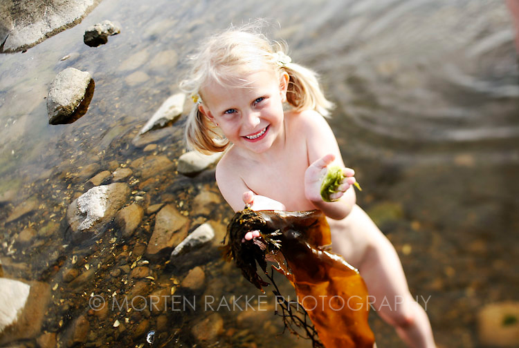Norway, girl (4-5) smiling with waste in hand, portrait
