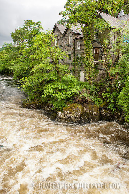 Betws-y-Coed Afon Llugwy River Snowdonia. The Afon Llugwy (River Llugwy) rapids flowing through Betws-y-Coed after particularly heavy rainfall. Betws-y-Coed is a small village in the heart of the Snowdonia National Park that is a popular base for hikers.