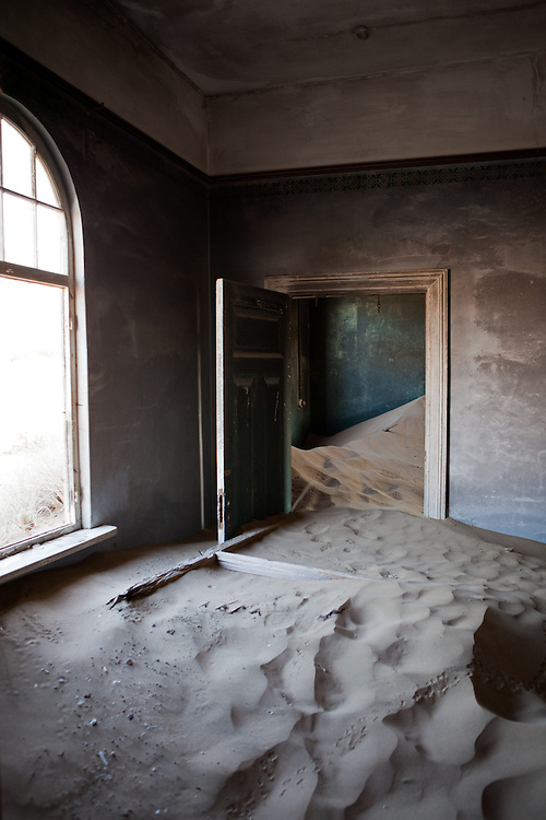 Sand fills a room in a home with decorated walls, evoking waves, in Kolmanskop, Namibia