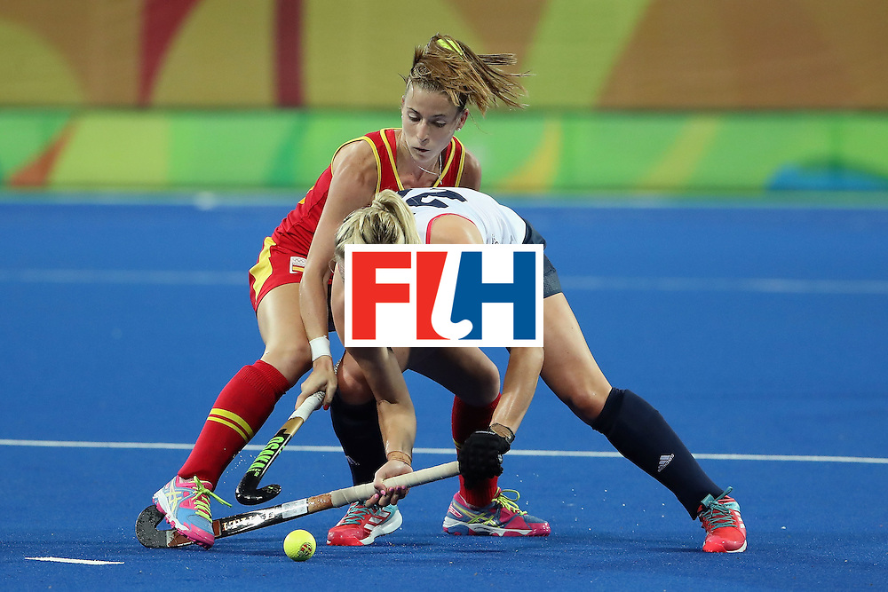 RIO DE JANEIRO, BRAZIL - AUGUST 15:  Hollie Webb #20 of Great Britain protects the ball from Berta Bonastre #10 of Spain during the first half of the quarter final hockey game on Day 10 of the Rio 2016 Olympic Games at the Olympic Hockey Centre on August 15, 2016 in Rio de Janeiro, Brazil.  (Photo by Christian Petersen/Getty Images)