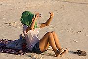 Thai toursist photographing sunset at Pattaya beach.