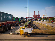 "12 FEBRUARY 2019 - SIHANOUKVILLE, CAMBODIA: A fruit vender who serves drivers going into the Sihanoukville port. There are about 50 Chinese casinos and resort hotels either open or under construction in Sihanoukville. The casinos are changing the city, once a sleepy port on Southeast Asia's ""backpacker trail"" into a booming city. The change is coming with a cost though. Many Cambodian residents of Sihanoukville  have lost their homes to make way for the casinos and the jobs are going to Chinese workers, brought in to build casinos and work in the casinos.       PHOTO BY JACK KURTZ"
