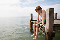 Pre-teen boy sitting on end of pier with feet in water portrait