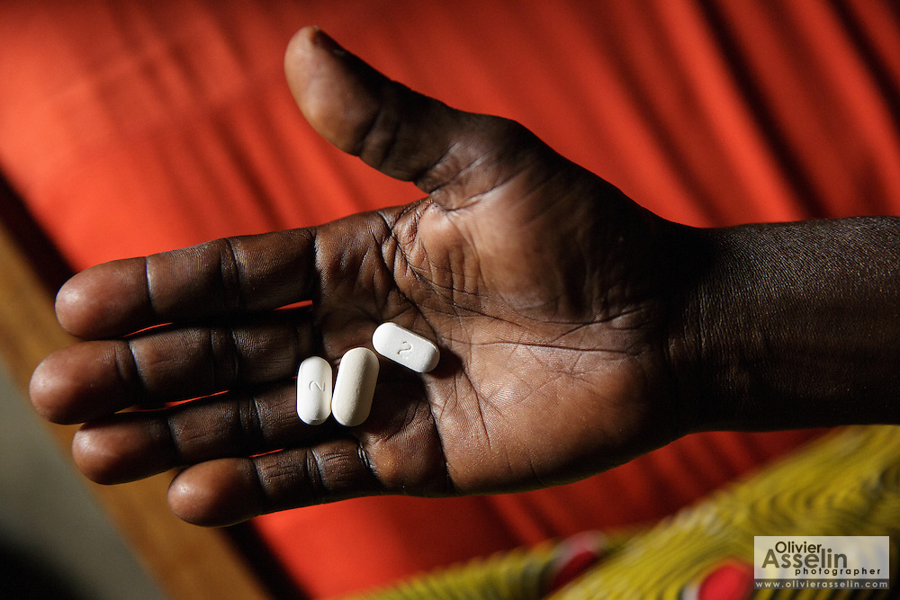 Adjua Yao, 45, who is HIV positive, holds the drugs she takes every day as she sits in a room of her sister's home in the Campement neighborhood of Abidjan, Cote d'Ivoire on Wednesday July 10, 2013. Adjua, a mother of five, is currently unemployed and lives with her sister. She's under ARV treatment and takes three pills a day.