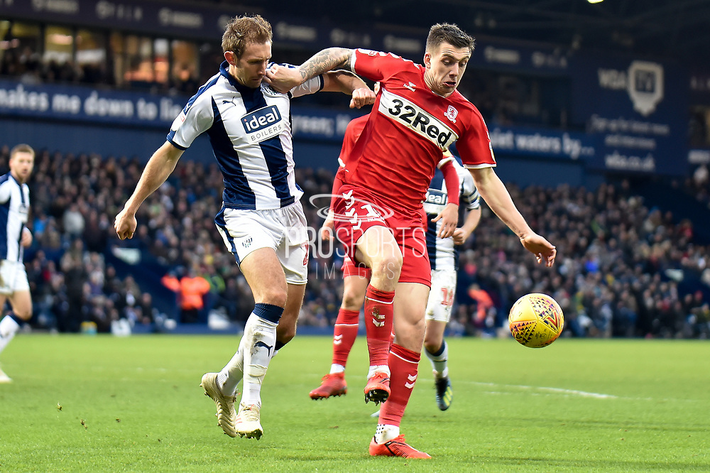West Bromwich Albion defender Craig Dawson (25) battles for possession  with Middlesbrough striker (on loan from West Ham United) Jordan Hugill (11) during the EFL Sky Bet Championship match between West Bromwich Albion and Middlesbrough at The Hawthorns, West Bromwich, England on 2 February 2019.