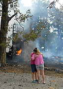 Vickie Slinkard, right, hugs daughter Chariti Lillibridge as they watch the historic log cabin they were restoring burn to the ground on Tuesday, August 31, 2010, on County Road 332. Jackson, Gordonville, Millersville, and Whitewater firefighters responded to the fire around 2:30 p.m. No one was injured.