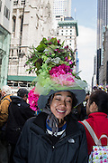 New York, NY, USA-27 March 2016. A young woman with a tall hat with flowers and greenery in the annual Easter Bonnet Parade and Festival.