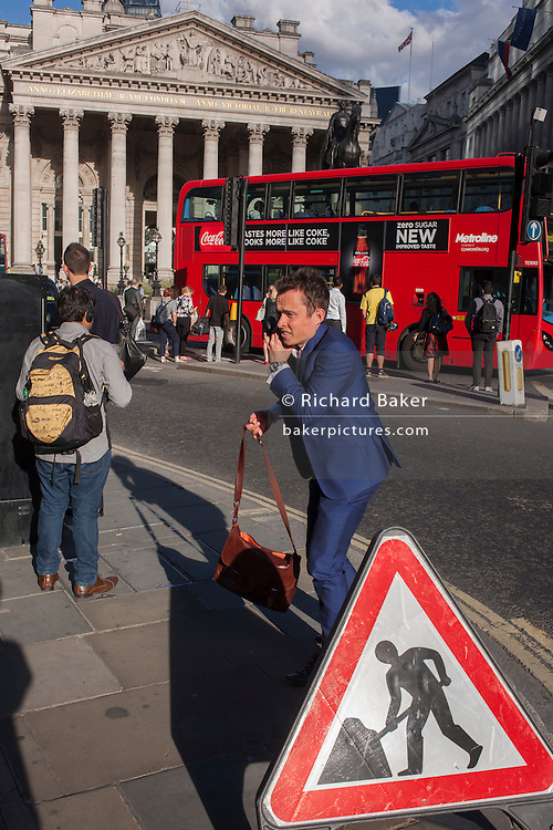 A man next to a Man At Work traffic sign, stands up after crouching on the bust street in the City of London, England UK.