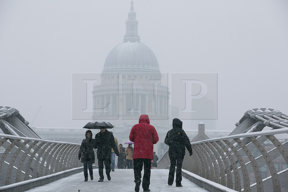 © Licensed to London News Pictures.20_01_2013 LONDON UK.Tourist and site see-ers cross the River Thames on the Millennium Bridge.Heavy Snow fall on the third day of  freezing cold weather over most of the country. Photo credit : Andrew Baker/LNP