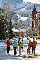 Skiers walk through Whistler Village on a sunny winter day, carrying their skis.