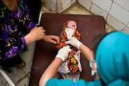 A newborn baby is wrapped in a sheet before being handed over to her grandmother. Faizabad, Badakshan, Afghanistan, 2012