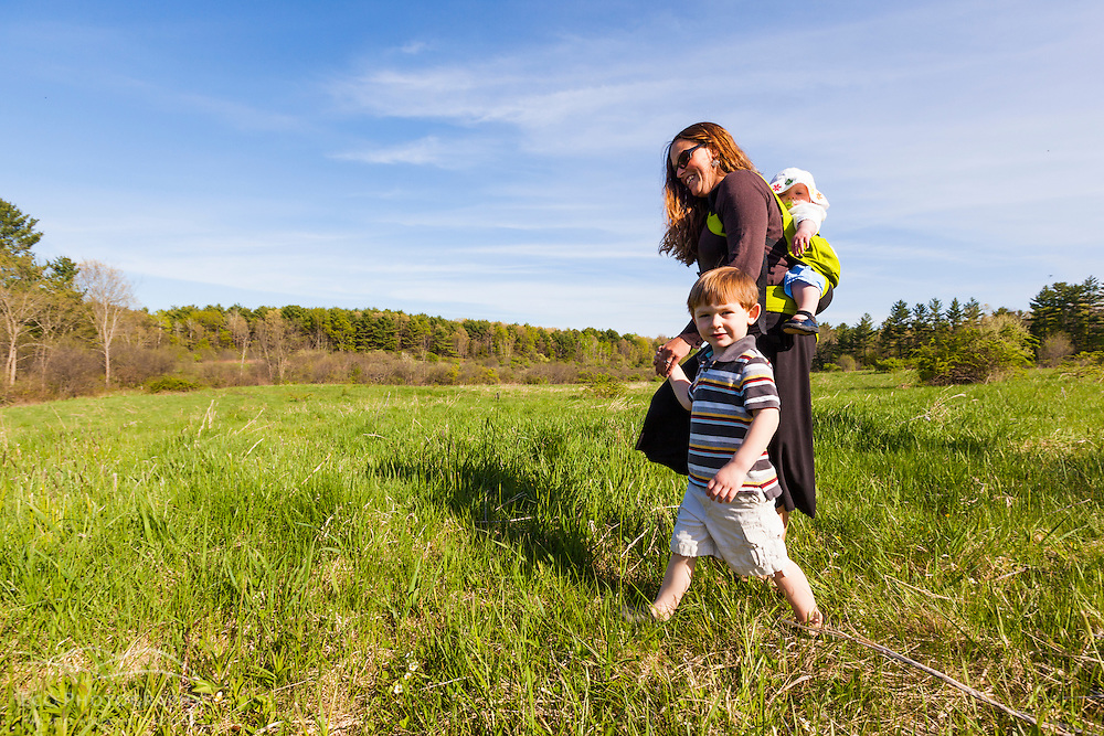 A woman and her young children explore a field in Durham, New Hampshire.