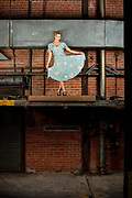 Model Brenna Smith, in a vintage 1940s dress and hair, poses on a conveyor in an abandoned factory.