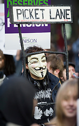 © Licensed to London News Pictures. 30/11/2011. London, UK. A man wearing a Guy Fawkes mask taking part in the march.  Workers and Union members take part in a national public sector worker strike in central London today (30/11/2011). Up to two million public sector workers are staging a strike over pensions in what is set to be the biggest walkout for a generation.  Ben Cawthra/LNP