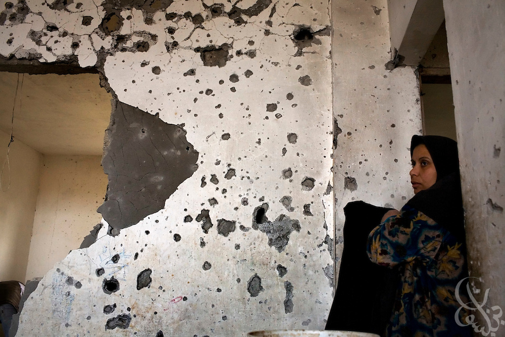 A Palestinian woman removes household items from her destroyed home in Beit Lahiya in the northern Gaza Strip January 19, 2009. Many residents returned to find destroyed or severely damaged homes following a cease-fire agreement Saturday night. According to the United Nations and Palestinian officials, more than 4,000 homes were destroyed during the Israeli operation.