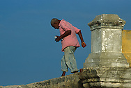 Un anciano con sus jeans arremangados en las piernas, camina sobre los altos muros de la muralla. Haciendo equilibrio con el azul del cielo fondo, trata de llevar lo que tiene bien agarrado en su mano hasta algún destino final. Cartagena de Indias, 2001 (Ramón Lepage / Orinoquiaphoto)     The fortified wall of Cartagena is in excellent condition and stretches more-or-less unbroken round a good portion of the Old Town. It is a pleasure for locals well as visitors to walk and observe the colonial architecture and excellent view of the Caribbean ocean..