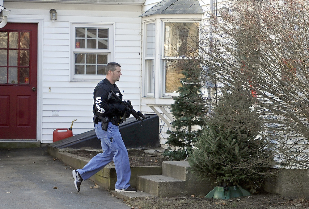 A police officer checks a home near the Sandy Hook Elementary School after a shooting at the school in Newtown, Conn. where a gunman opened fire, leaving 26 people dead, including 20 children, Friday, Dec. 14, 2012. (AP Photo/Jessica Hill)