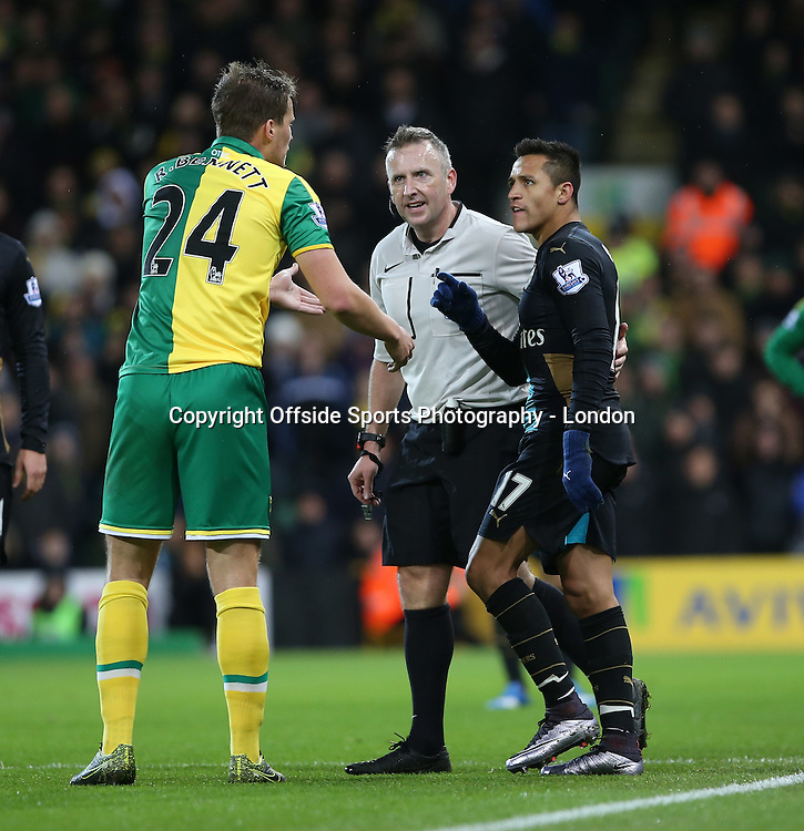 29 November 2015 Premier League Football : Norwich City v Arsenal : Alexis Sanchez accuses Norwich defender Ryan Bennett of pushing into the perimeter fence.<br /> <br /> Photo: Mark Leech