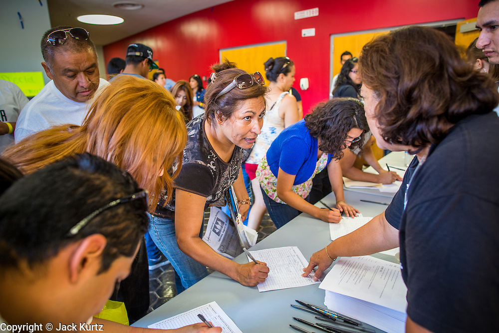 "25 AUGUST 2012 - PHOENIX, AZ: Immigrants sign into the deferred action workshop Saturday. Hundreds of people lined up at Central High School in Phoenix to complete their paperwork to apply for ""Deferred Action"" status under the Deferred Action for Childhood Arrivals (DACA) program announced by President Obama in June. Volunteers and lawyers specialized in immigration law helped the immigrants complete the required paperwork. Under the program, the children of undocumented immigrants brought to the US before they turned 16 years old would not be subject to deportation if they meet a predetermined set of conditions.     PHOTO BY JACK KURTZ"