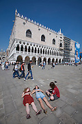 Asian tourists next to St. Mark's Square in front of Palazzo Ducale.