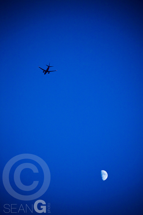 A 737 jet flies over the moon on a blue night sky in Dallas, Texas