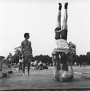 Acrobatic partners demonstrating balance in an open space, Glastonbury, Somerset, 1989