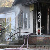 A Tupelo fire fighter soaks down the front porch area at a house fire on the 100 block of South Highland Drive in Tupelo Tuesday afternoon.