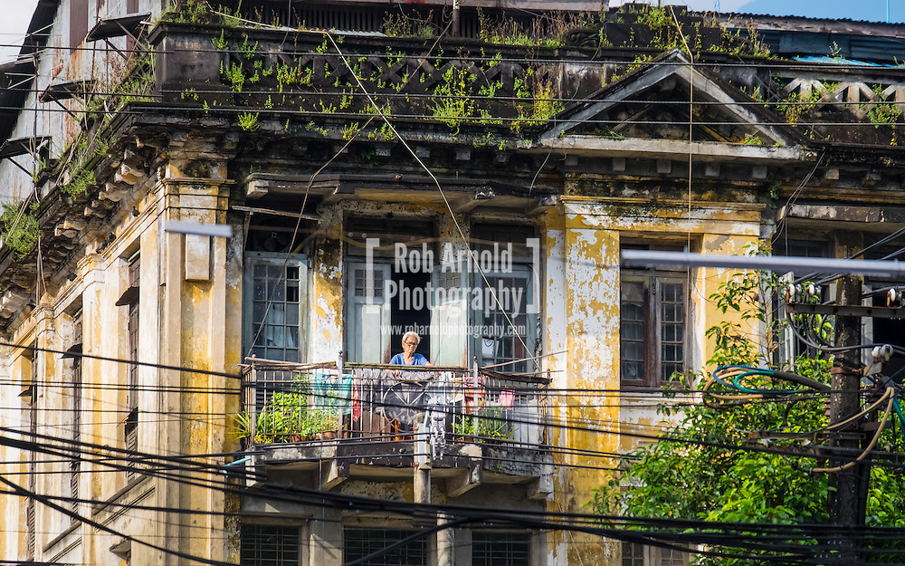 A woman hanging washing on her balcony in Downtown Yangon