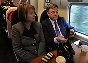 © Licensed to London News Pictures. 16/03/2012. London, UK.  Harriet Harmen and Ed Balls MP look at a tablet computer. Leader of the Labour Party, Ed Miliband and members of his Shadow Cabinet travel to Labour's Youth Conference in Coventry this morning, 16 March 2012, by train from London Euston Station. Photo credit : Stephen SImpson/LNP