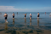 Bathers socially distance while wading out from the beach and into the shallows of the Thames Estuary, on 18th July 2020, in Whitstable, Kent, England.
