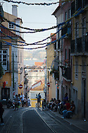 People on the streets of the Bica neighborhood, with the decorations of the Santo Antonio festivities hanging from the balconies.