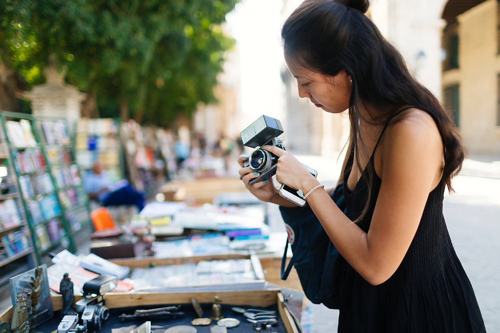 20 something looks to buy an antique camera at a flea market in Old Havana, in Havana Cuba