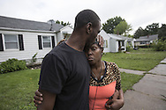 Arkiess Washington gets a kiss from her son, James Jackson after seeing the flooding damage to her home along Frederickson Street in South Bend, Ind., Tuesday, Aug. 16, 2016. (Santiago Flores/South Bend Tribune via AP)