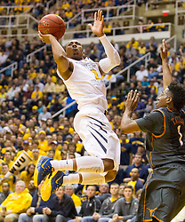 West Virginia Mountaineers guard Jevon Carter (2) makes a move and scores against the Texas Longhorns during the second half at the WVU Coliseum.