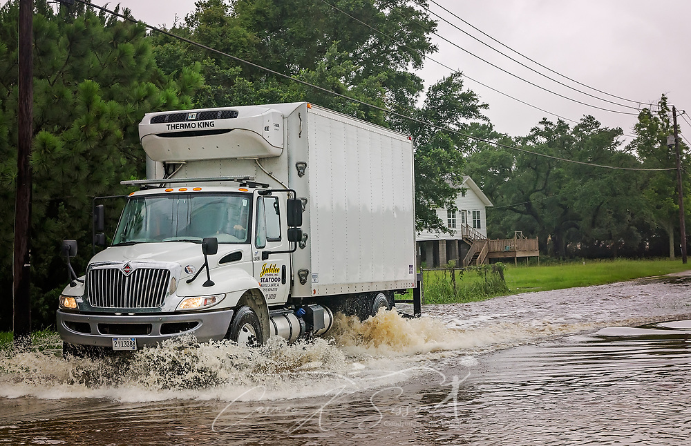 A driver for Jubilee Seafood makes his way down Shell Belt Road, June 22, 2017, in Bayou La Batre, Ala. The bayou experienced significant flooding along Shell Belt Road following heavy rains caused by Tropical Storm Cindy. The tropical storm made landfall at daybreak near Lake Charles, La., leaving one person dead and a drenched Gulf Coast, from Texas to Florida, in its wake. (Photo by Carmen K. Sisson/Cloudybright)
