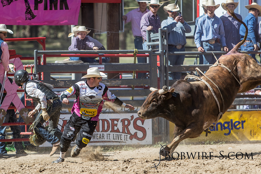 Bullfighter Nate Jestes comes to the rescue of bull rider JW Griffin in the first performance of the Elizabeth Stampede on Saturday, June 2, 2018.