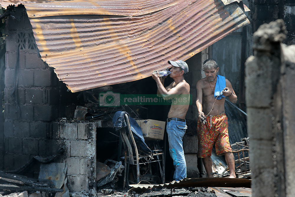 June 22, 2017 - Residents look for reusable materials from their burnt home after a fire at a residential area in Manila, the Philippines. More than 100 shanties were razed in the fire, leaving 200 families homeless. (Credit Image: © Rouelle Umali/Xinhua via ZUMA Wire)