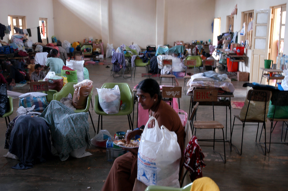 A woman whose homes was destroyed by the December 26, 2004 Tsunami which struck S.E. Asia following a 9.0 earthquake in the Indian Ocean eats a meal provided by relief operations in one of the buildings of the Batticaloa Hindu College where she now lives..Batticaloa, Sri Lanka. 11/01/2005.Photo © J.B. Russell