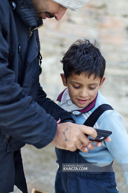 Kid watches his picture on a phone in a village in Kullu
