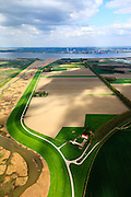 Nederland, Zeeland, Zeeuws-Vlaanderen, 09-05-2013; Hertogin Hedwigepolder met Verdronken Land van Saeftinghe links, gezien naar de Westerschelde en haven Antwerpen. Rechtsboven de Prosperpolder. In verband met de verdieping van de vaargeul van de nabijgelegen Westerschelde moet er volgens de Europese habitatrichtlijn natuurcompensatie komen. Door de polder en de Belgische Prosperpolder, aan de andere kant van de grens, te ontpolderen wordt er grond terug gegeven aan de natuur, zogenaamde natuurcompensatie. De maatregelen zijn omstreden, in het Belgisch deel van het gebied is men reeds begonnen..Hertogin Hedwigepolder with Drowned Land of Saeftinghe (left). Because of the future enlargement of the fairway of the nearby Westerschelde, the nature has to be compensated (according to the European Habitats Directive). The Hertogin Hedwige polder (and the adjacent Belgian polder - on the other side of the border - the Prosperpolder) are to be given back to nature, i.e. are to be 'de-polderd'. The measures are controversial, but in the Belgian part of the polders works have already been started..luchtfoto (toeslag op standard tarieven).aerial photo (additional fee required).copyright foto/photo Siebe Swart