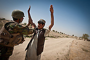 An Afghan National Army soldier searches an Afghan boy.